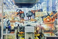 Robots que sueldan con autógena en una fábrica del coche Imagen de archivo libre de regalías