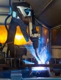 Robots que sueldan con autógena en una fábrica del coche Imagenes de archivo