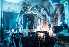 Robots que sueldan con autógena en una fábrica del coche Fotos de archivo