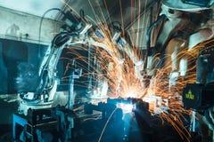 Robots que sueldan con autógena en una fábrica del coche Foto de archivo libre de regalías