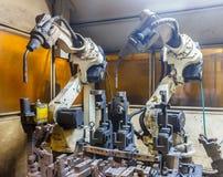 Robots que sueldan con autógena piezas automotrices Imagenes de archivo