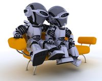 Robots on a sofa Stock Images