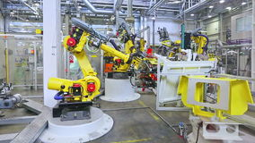 Robots and worker in a car factory stock video
