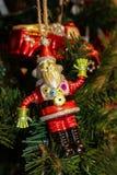 RobotSanta Christmas prydnad på den gröna julgranen med firetruckprydnaden i bakgrund arkivfoto