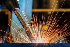 Robotsvetsning är svetsningmetalldelen i fabrik Royaltyfri Foto