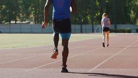 Robuster Sportler, der für Marathon, körperliche Bewegungen am Stadion tuend sich vorbereitet stock video