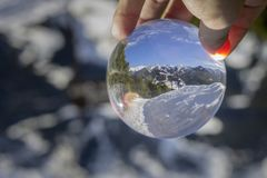 Roc Del Quer trekking trail, reflection view through crystal ball. Andorra. Roc Del Quer trekking trail reflection view through crystal ball. Principality of Stock Photo