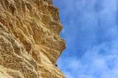 Roca amarilla contra el cielo azul fotografía de archivo