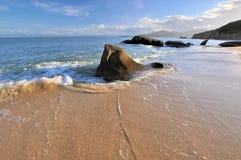 Roca de la costa de mar en la iluminación de la puesta del sol Imágenes de archivo libres de regalías