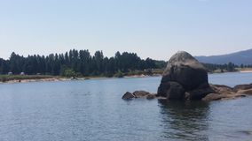 Roca de la isla en el lago azul Imagenes de archivo