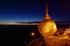 Roca de oro en el crepúsculo con la gente de rogación, pagoda de KyaiKhtiyo, Fotos de archivo
