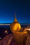 Roca de oro en el crepúsculo con la gente de rogación, pagoda de KyaiKhtiyo Fotografía de archivo