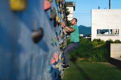 Roca de pared del hombre que sube joven al aire libre Fotos de archivo libres de regalías