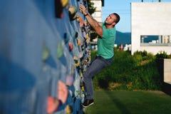 Roca de pared del hombre que sube joven al aire libre Imagen de archivo libre de regalías