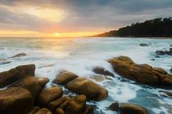 Roca del golpe de la onda en paisaje marino del tiempo de la puesta del sol Imagen de archivo