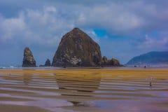 Roca del pajar que refleja en arena mojada durante la bajamar fotografía de archivo