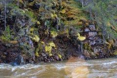 Roca demasiado grande para su edad con el musgo y el liquen cerca del agua fotos de archivo libres de regalías