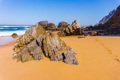 Roca en la costa costa de la playa arenosa de Adraga, costa de Portugal fotos de archivo