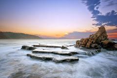 Roca en la playa de Azkorri en la puesta del sol Foto de archivo