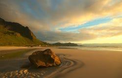 Roca en la playa de Sandy en el Sun de medianoche Imágenes de archivo libres de regalías