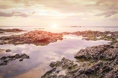 Roca en la playa y la puesta del sol Imagen de archivo libre de regalías