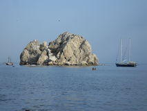 Roca en un mar y cortadores Imagenes de archivo