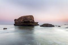 Roca enorme en la costa costa en la puesta del sol Imágenes de archivo libres de regalías