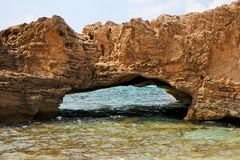 Roca escénica del arco en agua de mar Imagenes de archivo