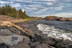 Roca grande en el mar y el bosque azules de la puesta del sol en la distancia foto de archivo libre de regalías