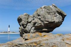 Roca masiva en una playa en Ile de Sein con el faro en t imagen de archivo