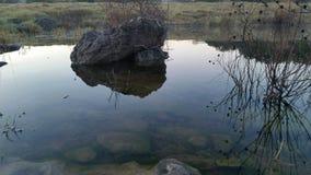 Roca mediana que se sienta en agua inmóvil Fotografía de archivo