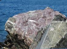 Roca púrpura en el océano Fotos de archivo libres de regalías