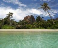 Roca, palma-árboles en la playa tropical del paradice. Foto de archivo