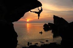 Roca que sube del hombre cerca del mar Foto de archivo