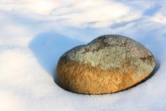 Roca solitaria rodeada por la nieve Imágenes de archivo libres de regalías