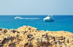 Roca volcánica en un fondo borroso del mar y de los barcos azules fotos de archivo libres de regalías