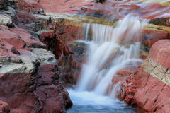 Roca y cascada rojas - lagos Waterton, Al Foto de archivo libre de regalías