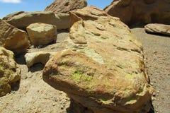 Rocas amarillas con el musgo verde Fotos de archivo