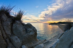 Rocas, arena, mar y una playa con una pequeña cueva en la puesta del sol, Sithonia Fotografía de archivo