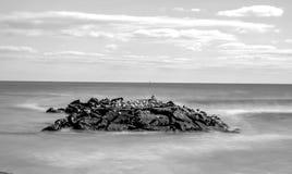 Rocas blancos y negros de la línea de la playa de la exposición larga Fotografía de archivo