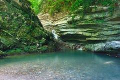 Rocas boscosas cubiertas con la hiedra y el musgo con la cascada que fluye abajo Imagenes de archivo
