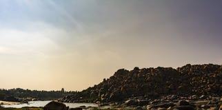 Rocas, cantos rodados con el templo del virupaksha en una esquina Hampi fotos de archivo