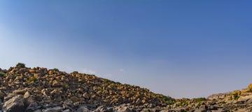 Rocas, cantos rodados en un fondo del cielo azul fotos de archivo