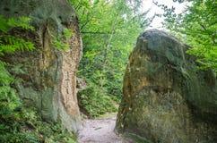 Rocas con una cruz descompuesta ellos en las puertas del monasterio en la cueva en las colinas cárpatas Rozhirche Fotografía de archivo libre de regalías
