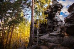 Rocas contra el cielo azul y el bosque fotografía de archivo