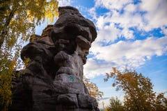 Rocas contra el cielo azul y el bosque imagenes de archivo