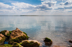 Rocas cubiertas de musgo encendido en el lago fotografía de archivo