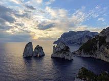 Rocas de Faraglioni que se elevan para arriba de las aguas mediterráneas azules brillantes en la isla de Capri, Italia fotografía de archivo