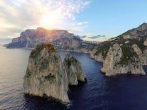 Rocas de Faraglioni que se elevan para arriba de las aguas mediterráneas azules brillantes en la isla de Capri, Italia fotografía de archivo libre de regalías