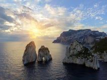 Rocas de Faraglioni que se elevan para arriba de las aguas mediterráneas azules brillantes en la isla de Capri, Italia imagenes de archivo